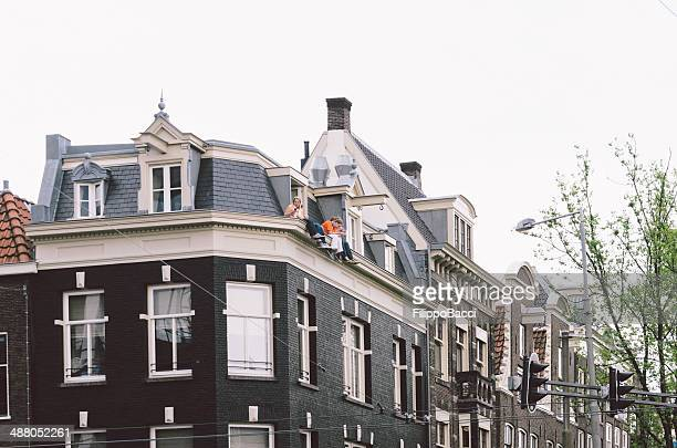 People sitting on a roof during Koningsdag 2014 in Amsterdam