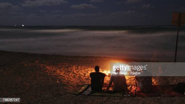 People Sitting On Beach Against Sky During Sunset