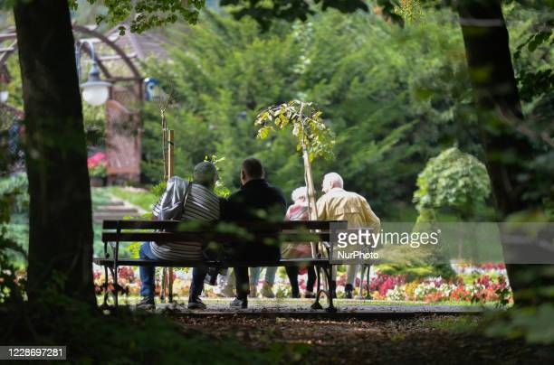 People sitting on benches in a park, in Rymanow-Zdroj. In the era of coronavirus, many health resorts suffer from a lack of patients. An admission...