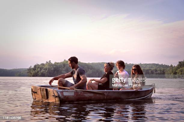 people sitting on boat in lake against sky during sunset - quatre personnes photos et images de collection