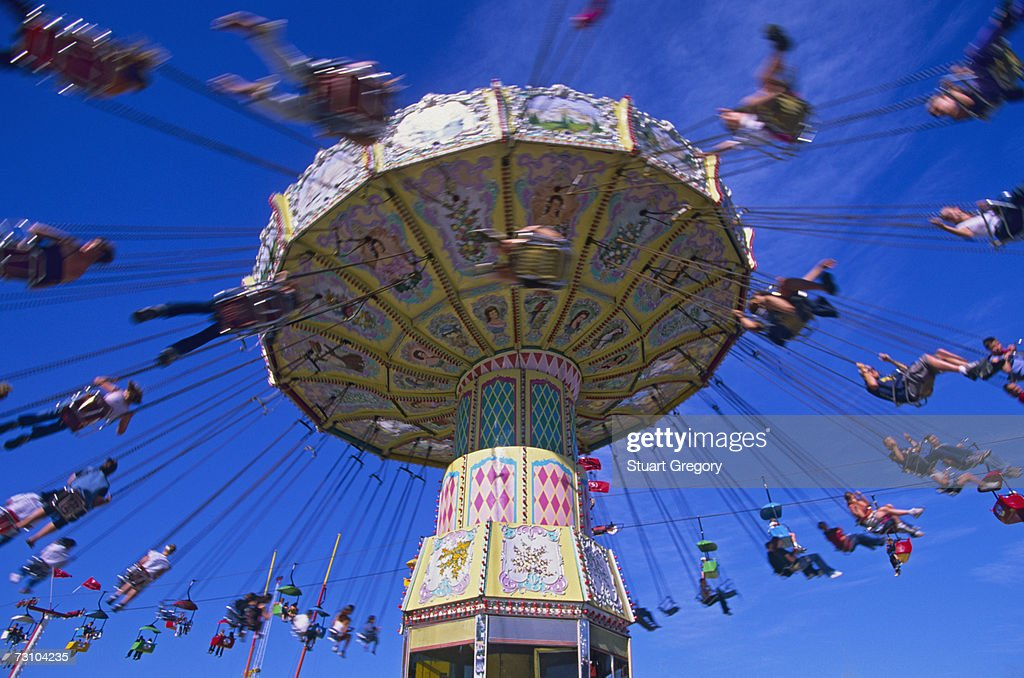 People sitting on carousel swings ride, low angle view : Stock Photo