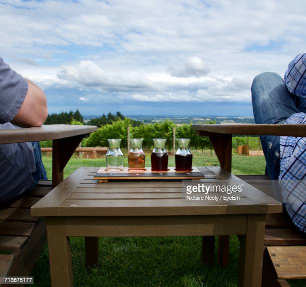 People Sitting On Chair By Table Against Sky