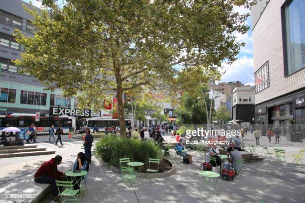 people sitting on chairs at the newly remodeled albee square by the fulton street mall in fort greene, brooklyn, new york city - fort greene stock pictures, royalty-free photos & images