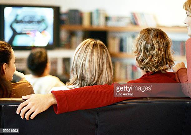 People sitting on couch watching TV, rear view.