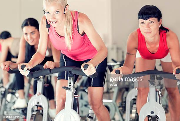 People sitting on spinning bikes in gym