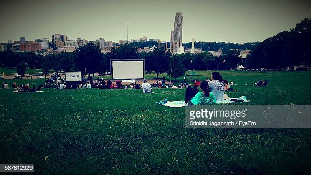 People Sitting On Grassy Field In Park At City Against Clear Sky