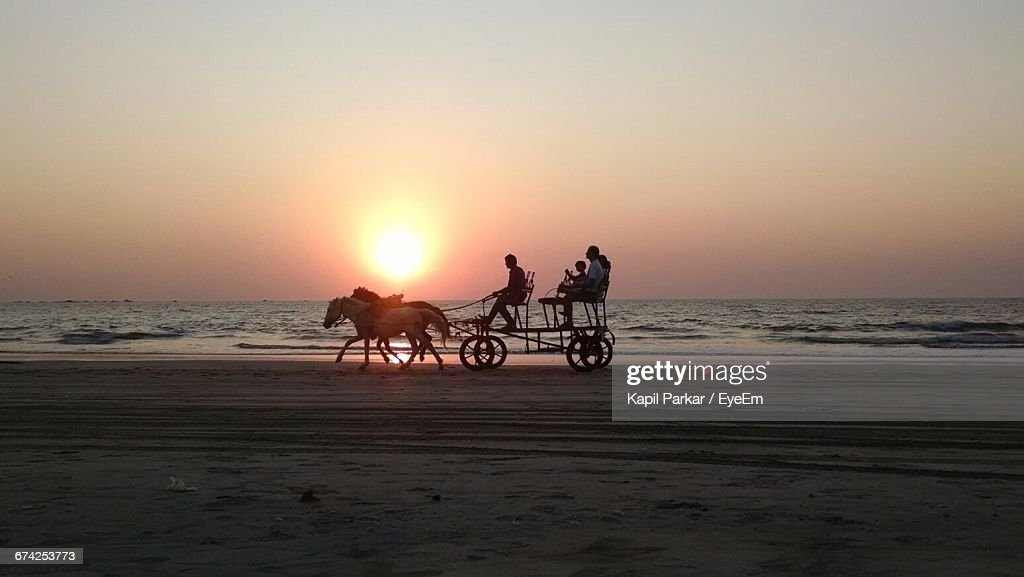 People Sitting On Horse Cart At Tarkarli Beach Against Clear Sky During Sunset : Stock Photo