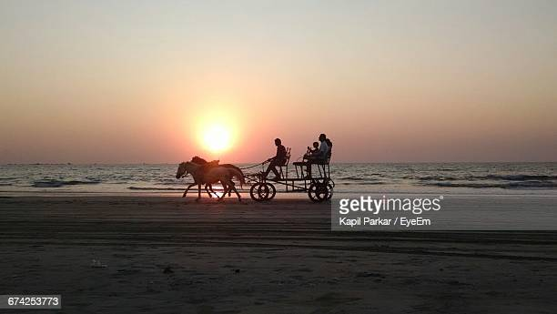 People Sitting On Horse Cart At Tarkarli Beach Against Clear Sky During Sunset