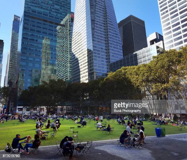 people sitting on metal chairs on the lawn in bryant park, in midtown manhattan at 42nd street between 5th and 6th avenue - bryant park stock pictures, royalty-free photos & images
