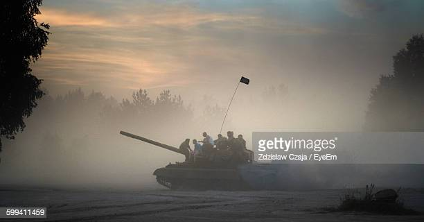 People Sitting On Military Tank In Foggy Weather Against Sky At Borne Sulinowo