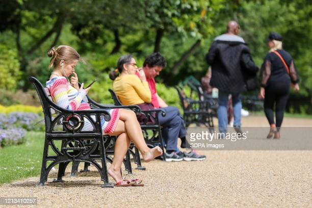 People sitting on park benches on a warm and sunny day in Finsbury park during the COVID-19 lockdown as they observe social distancing. The...