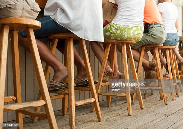 people sitting on stools at an outdoor bar - barstools - bare bum stock pictures, royalty-free photos & images