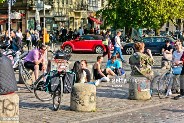 people sitting on street at admiralbrücke in berlin kreuzberg - kreuzberg stock photos and pictures