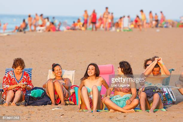 People sitting on the beach in front of the sun in Denia, El Palmar, Spain, August 2014
