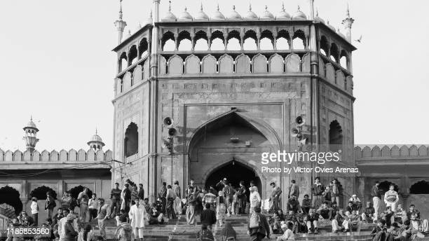 people sitting on the steps of the main gate entrance to jama masjid mosque in delhi, india - victor ovies fotografías e imágenes de stock