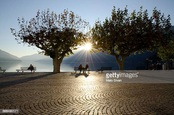 people sitting on the waterfront - ascona stock photos and pictures