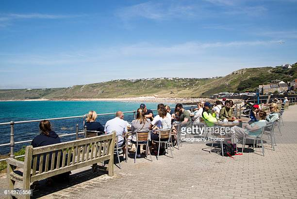 People sitting outdoors at cafe tables by the sea Sennan Cove Land's End Cornwall England UK