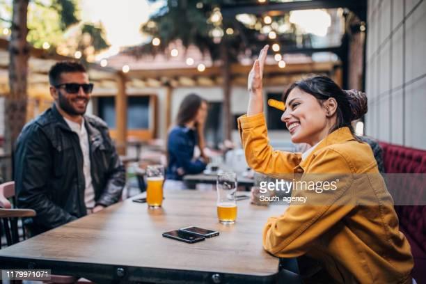 personnes s'asseyant à l'extérieur dans le pub - terrasse de café photos et images de collection