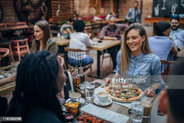 people sitting outdoors in restaurant - pizzeria stock pictures, royalty-free photos & images