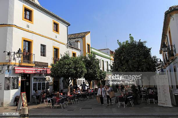 People sitting outdoors tables and chairs of restaurants in old part of city center Cordoba Spain