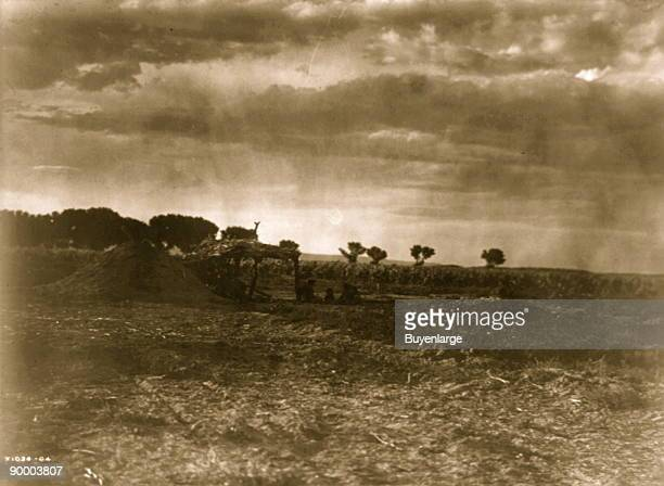 People sitting outside a brush canopy in front of an earth Hogan with background of arid land showing cornfield and short broad trees
