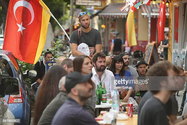 People sitting outside a restaurant in Kreuzberg district watch Germany play against Northern Ireland in the 2016 UEFA European Championship on June...