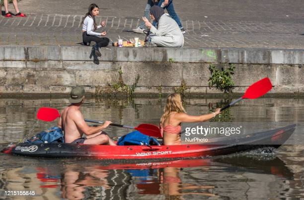 People sitting outside in social distance with the 1.5 meter standard in Ghent - Belgium on 25 May 2020.Belgium began to relax some of its lockdown...