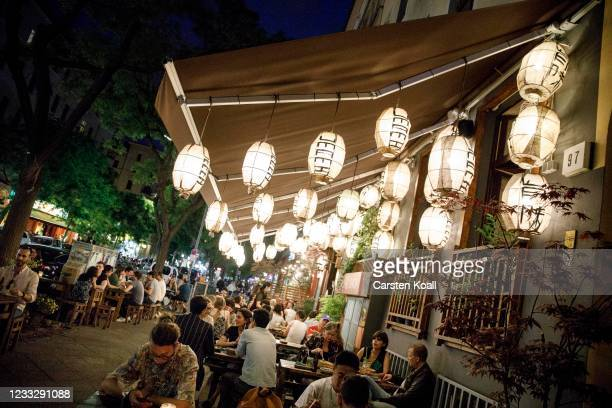 People sitting outside of a restaurant in Kreuzberg on the second day that people are no longer required to show a negative Covid test result to...