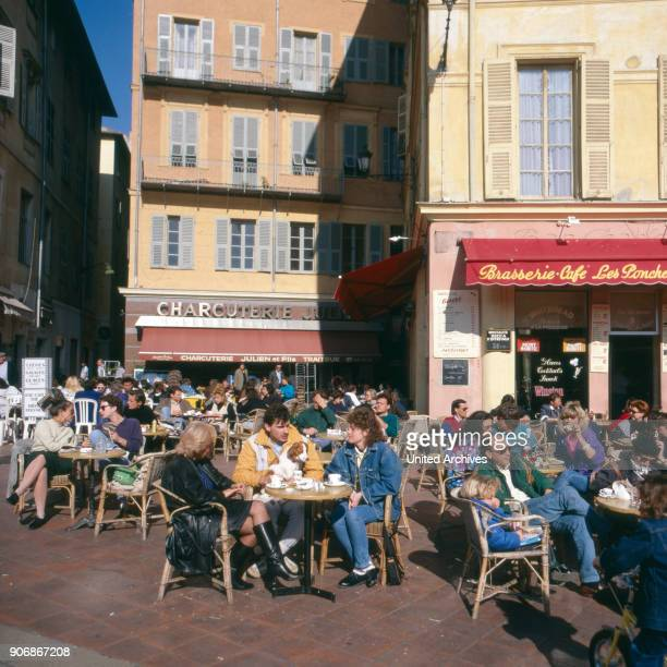 People sitting outside of a street cafe at Cannes France 1980s