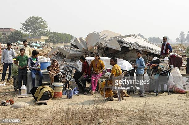 People sitting outside their houses demolished in anti-encroachment drive by Greater Noida Authority at Kulsera village on November 17, 2014 in...