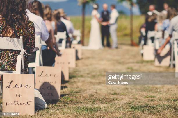 people sitting while young couple getting married by priest during sunny day - wedding vows stock pictures, royalty-free photos & images
