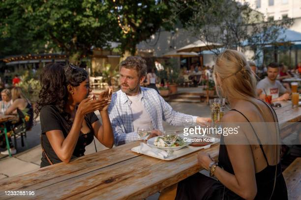 """People sittting together in the beer garden in the """"Cafe am neue See"""" on the second day that people are no longer required to show a negative Covid..."""