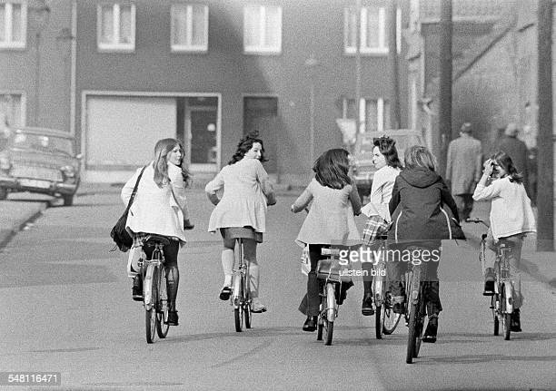 people six young girls on bicycles drive side by on a traffic road pleasure trip excursion aged 13 to 16 years