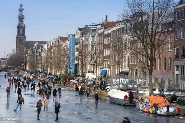People skate on the ice at the frozen canal 'Prinsengracht' in Amsterdam on March 2 2018 / AFP PHOTO / ANP / Evert Elzinga / Netherlands OUT
