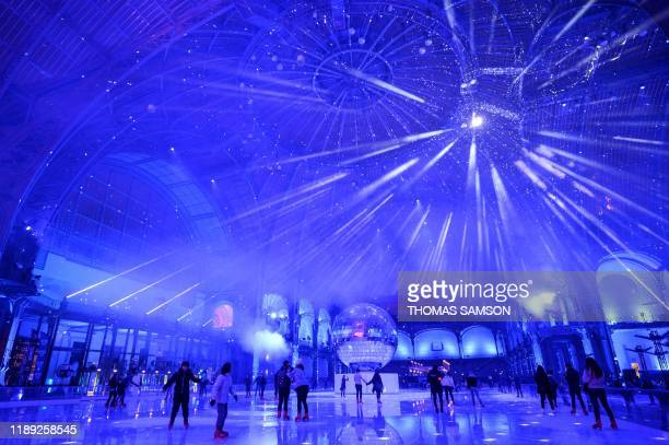 TOPSHOT People skate on the ice skating rink hosted at the glassroofed central hall of the Grand Palais in Paris on December 17 2019