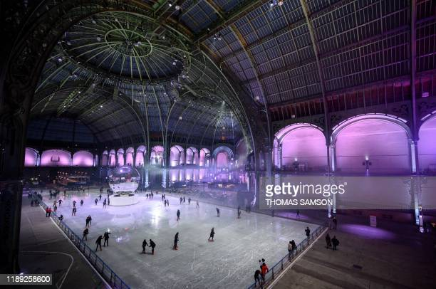People skate on the ice skating rink hosted at the glass-roofed central hall of the Grand Palais in Paris, on December 17, 2019.