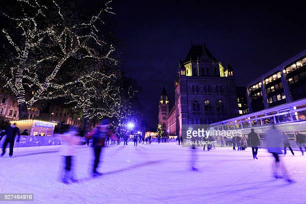 People skate on the temporary ice rink at the Natural History Museum London Each year around winter / Christmas time these ice rinks spring up in...