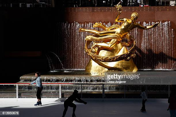 People skate past the Prometheus statue on the ice rink at the Rockefeller Center October 11 2016 in New York City The iconic ice rink opened for its...