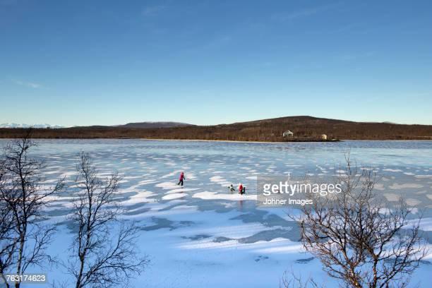 People skating on frozen lake