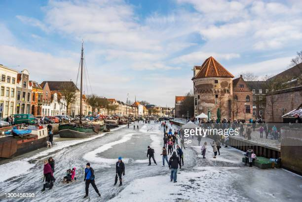 people skating on ice on the thorbeckegracht in zwolle, the netherlands during a beautiful winter day - winter sports event stock pictures, royalty-free photos & images