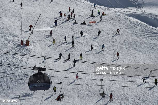 People ski down a slope at Val Thorens ski resort in the French Alps on January 5 2018 / AFP PHOTO / PHILIPPE DESMAZES