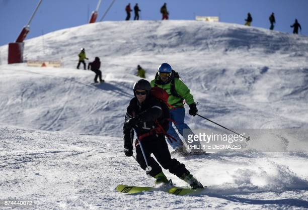 People ski during an execeptional opening at the ski resort of Courchevel on the French Alps following heavy snowfall on November 15 2017 / AFP PHOTO...
