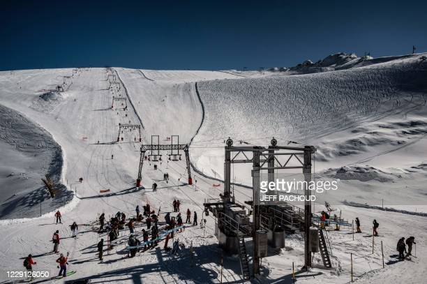 People ski on the opening day of the Les 2 Alpes French resort on October 17, 2020.