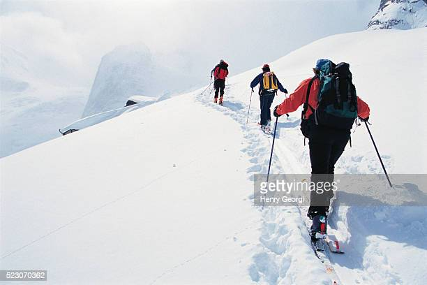 people ski touring in snowy mountains - back country skiing stock pictures, royalty-free photos & images
