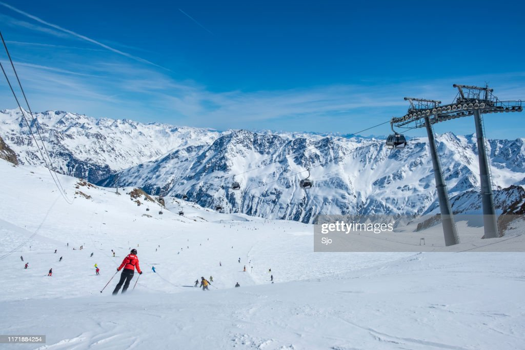 People skiing and snowboarding down a ski slope in the Sölden Ötztal ski area during a sunny winter day : Stock Photo
