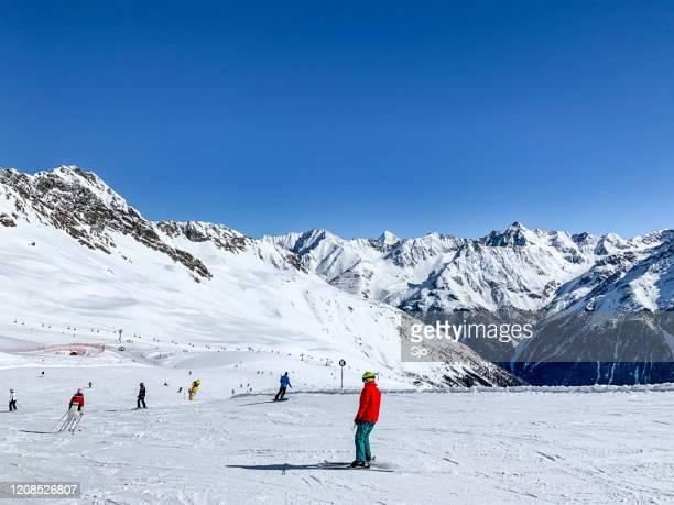 """mensen die onderaan een skihelling in het skigebied van sölden ötztal tijdens een zonnige de winterdag skiën en snowboarden - """"sjoerd van der wal"""" or """"sjo"""" stockfoto's en -beelden"""