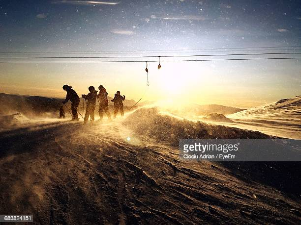 People Skiing On Mountain Against Sky During Sunset