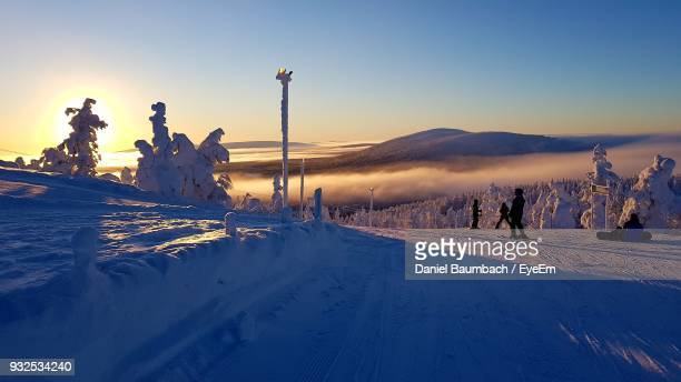 People Skiing On Snow Covered Field Against Sky During Sunset