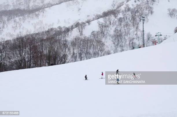 people skiing on snow covered field - hokkaido stock pictures, royalty-free photos & images
