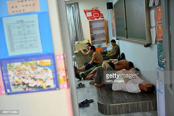 People sleep in a classroom at a primary school set as the emergency evacuation after the Wednesday explosions of a warehouse in Binhai New Area on...